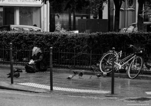 Une vieille dame assise sous la pluie sort un peu de pain de son sac. Peu importe qu'il fasse froid, qu'il pleuve ou qu'elle ne sache pas où dormir. Elle est heureuse de passer un peu de temps avec les seuls êtres qui sont proches d'elle.